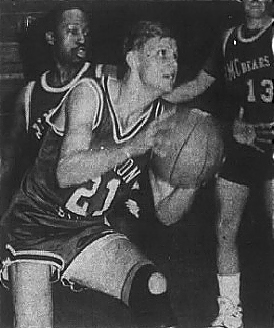 Image of college basketball player, Josh Robinson, number 21, Chadron State, shown about to launch a shot to our right. From the Chadron Record, Chadron, Nebraska, December 5, 1989.