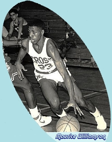 Image of boys basketball player, Maurice WIlliamson, of WIlbur Cross High School (New Haven, Connecticut), number 23, in his white CROSS uniform, driving around a defender to his right. He scored 78points in one game on Feb. 13, 1988.