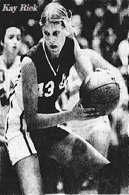Action shot of girls basketball player, Kay Riek, Grundy Center High School (Iowa), with ball, strategizing. In #13 uniform. From the Waterloo Courier, Waterloo, Iowa, February 27, 1980. Photo by Mary Kollath.