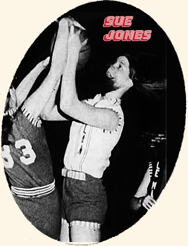 Picture of girls basketball player on the Heelan High Crusaders (Iowa) basketball team trying to pry ball, perhaps rebound from the arms of Le Mars High's Doris Reistroffer. Shown with hair in face. From The Sioux City Journal, Sioux City, Iowa, February 22, 1974.